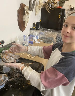 Melana Dupont, 14, creates resin keychains in her garage workspace. She sells her creations at the Las Cruces Farmers and Crafts Market through the Kids Can Jr. Vendors Program.