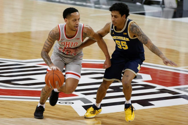 Ohio State's C.J. Walker, left, looks for an open pass as Michigan's Eli Brooks defends during the first half of an NCAA college basketball game Sunday, Feb. 21, 2021, in Columbus, Ohio. (AP Photo/Jay LaPrete)
