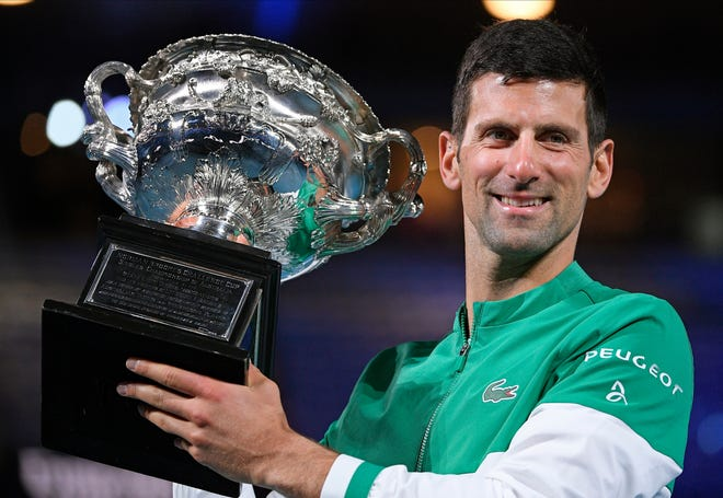 Serbia's Novak Djokovic holds the Norman Brookes Challenge Cup after defeating Russia's Daniil Medvedev in the Australian Open.