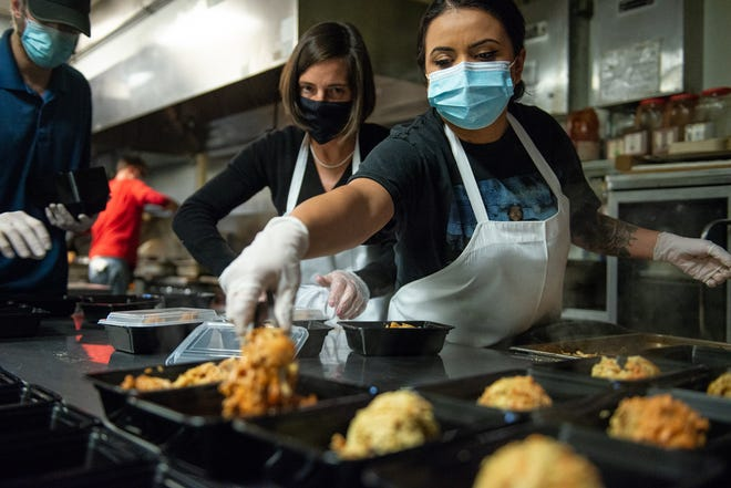 "Volunteer Ellen Gold, center, closes lids while Brittany Salinas spoons lentils and chicken into to-go containers to be delivered to residents without power or water, shelters and emergency workers Thursday at Lighthouse Cuisine in Austin. The volunteers, calling themselves ""The Love Effort,"" prepared about 2,500 dinners that evening."