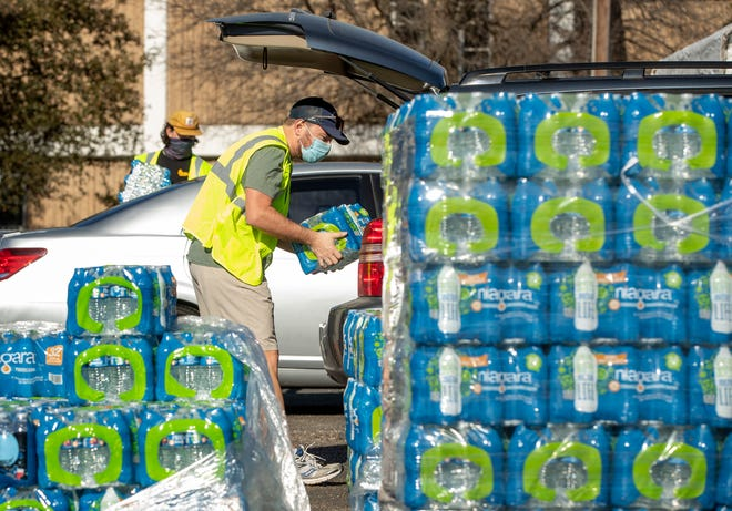 Volunteer James McDaniel loads a car with water at a water distribution site at Nelson Field in Northwest Austin on Monday. Austin Water officials said Tuesday that emergency water restrictions will be lifted Wednesday morning.