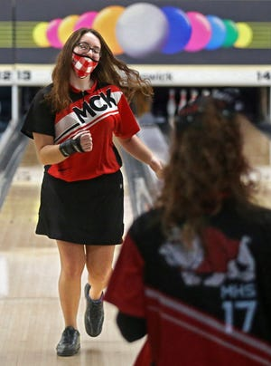 Canton McKinley junior Brooke Tucker pumps her fist as she walks back to her teammates after a strike during the Division I district bowling championship at Freeway Lanes of Warren on Monday. Tucker led the Bulldogs to the state tournament. [Jeff Lange/Beacon Journal]