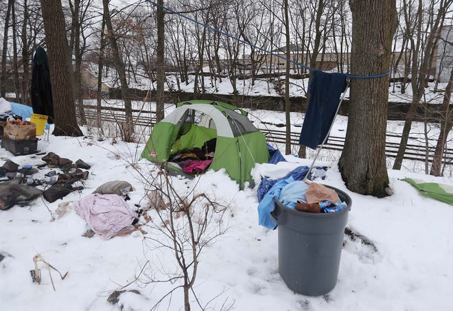 A small homeless encampment between Grace Park in Akron and the railroad tracks sits abandoned Monday.