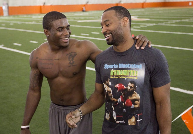 Texas football great Michael Huff, right, talks with fellow Texas ex Aaron Williams at Pro Timing Day in 2011. Huff and other alumni lent an able assist to families in need during the winter storm the past week.
