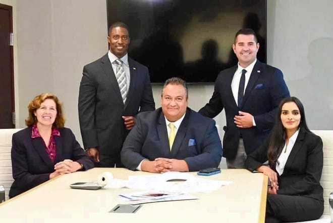 The Mount Laurel Township Council. From left: Councilwoman Karen Cohen, Deputy Mayor Kareem Pritchett (standing), Councilman Nick Moustakas (sitting in middle), Mayor Stephen Steglik (standing) and  Councilwoman Fozia Janjua.