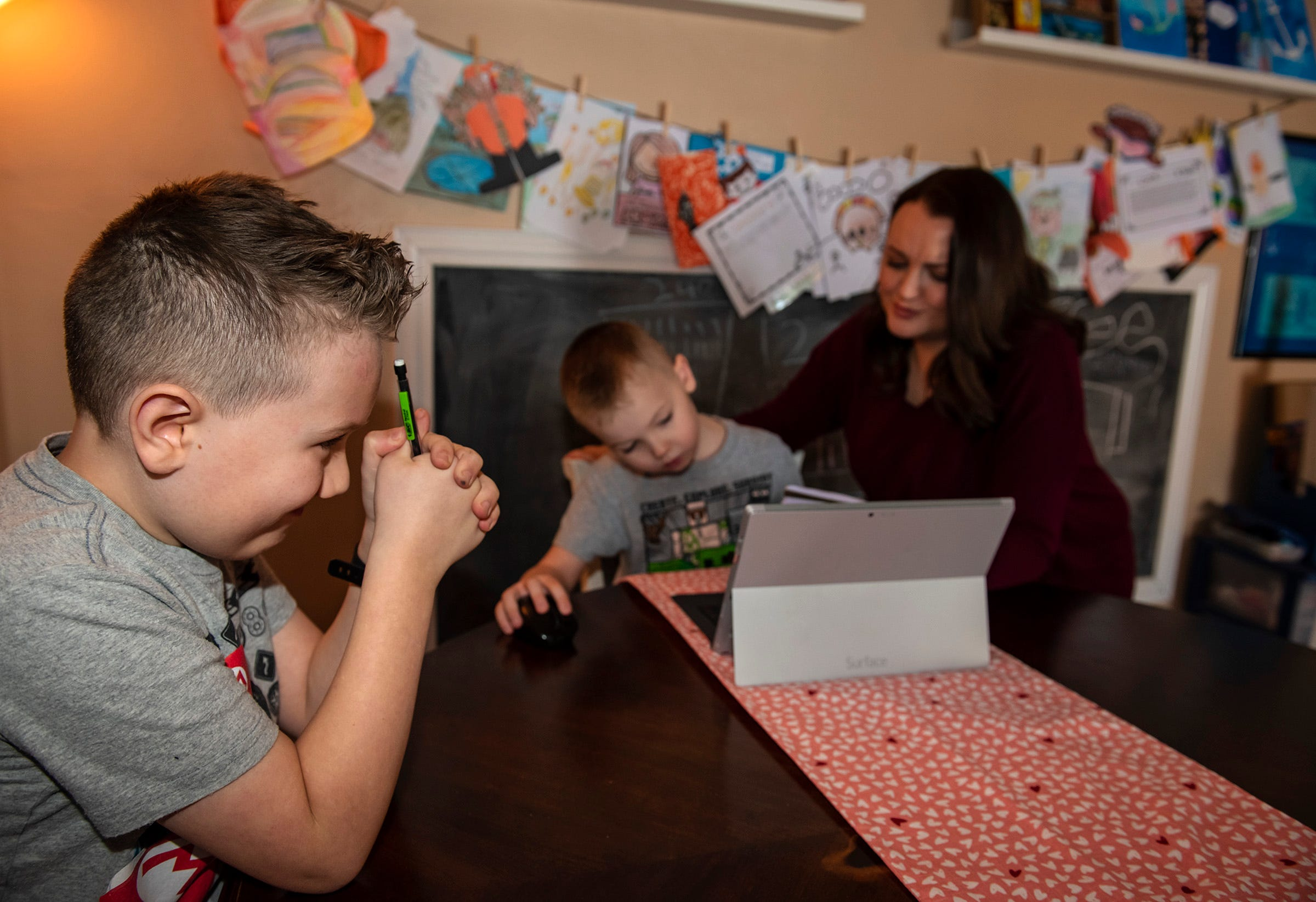 Cameron Baughman, 8, left, thinks hard about a multiplication problem given him by his mom, Jamie Baughman, who is also helping her younger son Gage, 6, do his homework in their Rochester Township home.