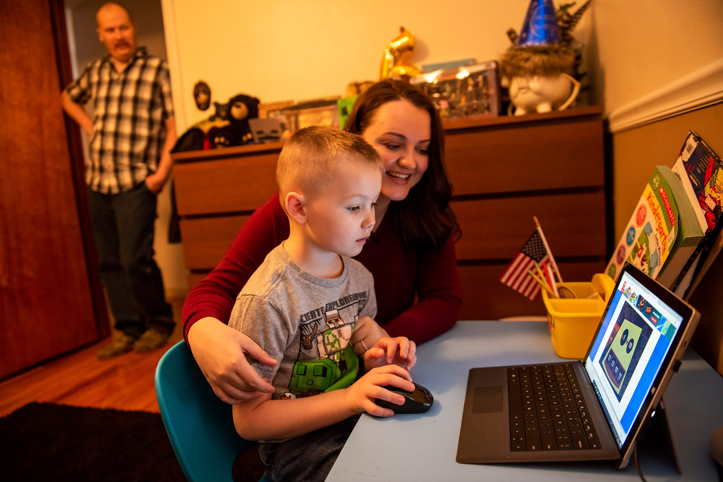 """Zak Baughman watches his wife, Jamie, help their son Gage, 6, do his homework in their Rochester home. """"I want to get my kids back out into the world,"""" Jamie Baughman said."""