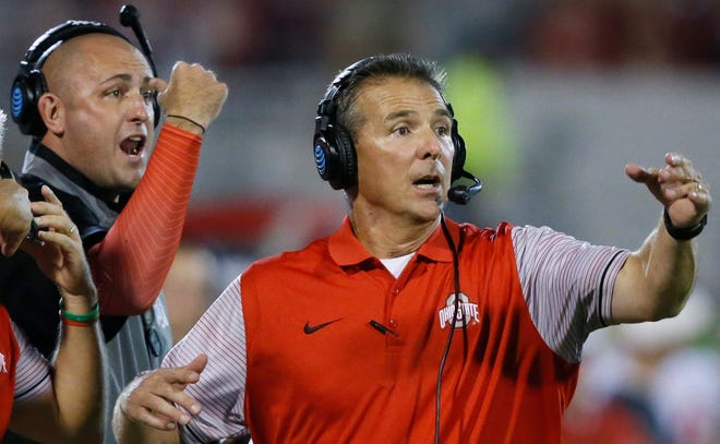 In this Sept. 17, 2016, file photo, former Ohio State head coach Urban Meyer, right, and then-assistant coach Zach Smith, left, gesture from the sidelines during a football game against Oklahoma.