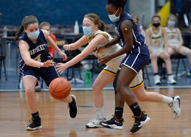 Nantucket's Raegen Perry, left, and Kamoy Barnett, right, battle for the ball with Nauset's Sophie McIsaac, center, during a second-quarter play on Monday. To see more photos, go to www.capecodtimes.com.