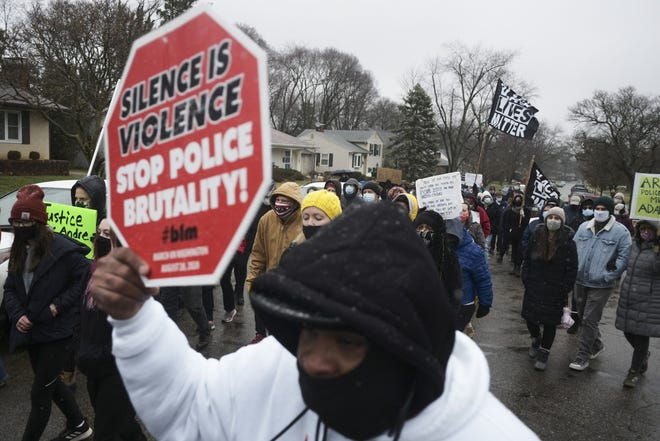 Residents and supporters march up Oberlin Drive during a vigil for Andre Hill on Dec. 24. Hill, a 47-year-old Black man, was shot and killed by Columbus police officer Adam Coy. Hill was unarmed.