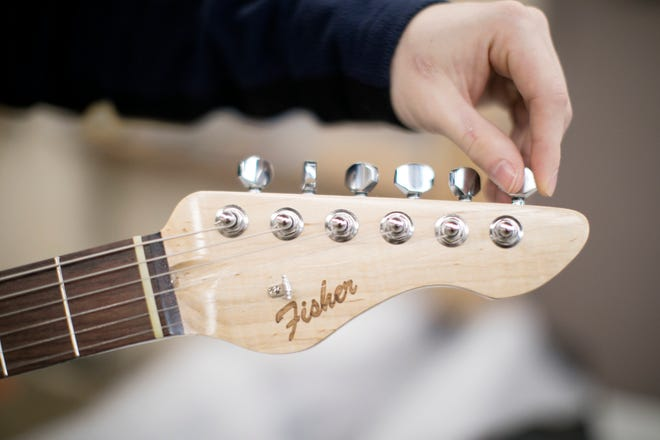 """Ben Fisher adjusts the tuning pegs, or machine heads, on his custom Fender Stratocaster replica. He etched his name, now his """"brand,"""" in the Fender logo style on the head stock."""