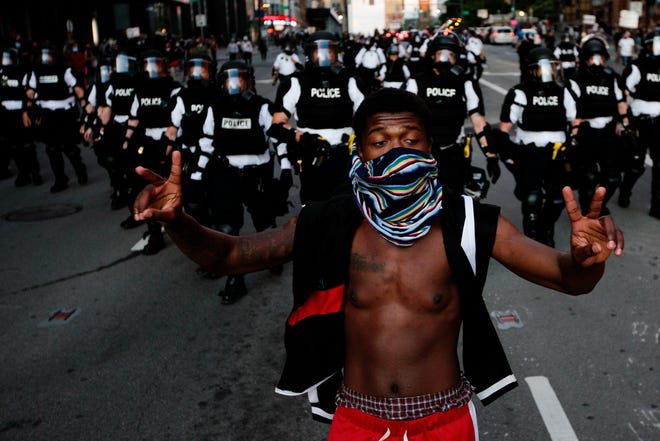 A protester walks down Broad Street as Columbus Division of Police officers walk behind during nationwide protests following the death of George Floyd, a black man in Minneapolis who died while in police custody earlier this week, on Friday, May 29, 2020 in Columbus, Ohio.