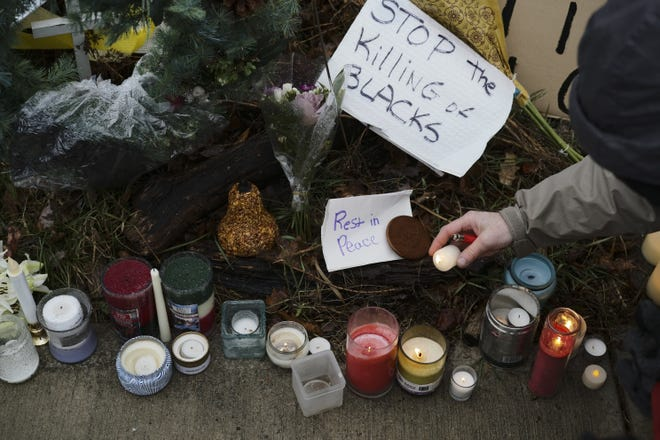 Cranbrook resident Joe Stone lights candles at a makeshift memorial Dec. 24 near where Andre Hill, an unarmed Black man, was fatally shot by then-Columbus police officer Adam Coy.