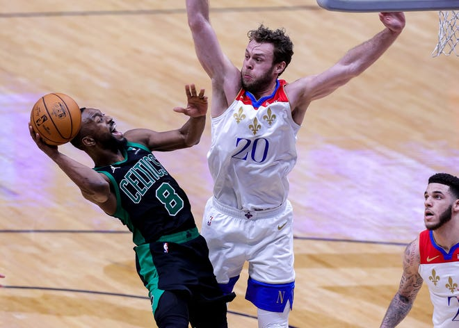 Feb 21, 2021; New Orleans, Louisiana, USA;   Boston Celtics guard Kemba Walker (8) shoots a jump shot against New Orleans Pelicans forward Nicolo Melli (20) during the second half at Smoothie King Center.