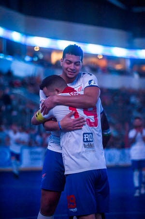 Kansas City Comets forward Rian Marqes, back, gets a hug from teammate John Sosa after scoring a goal in the second half of Sunday's game at Cable Dahmer Arena. Marques scored two goals to help the Comets to a 13-4 win.