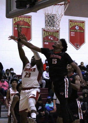 Jackson forward James Morrow (15) leaps to block a shot by Bishop Snyder forward Moise Balungu during a Jan. 12 game. Jackson and Bishop Snyder meet again in Tuesday's regional semifinal.