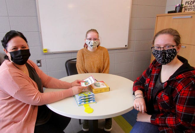 Sarah Boone, left, principal at Millikin Grade School in Geneseo; Alyssa Gentry and Abby Gentry, Geneseo High School students involved in the Extended School Day program at Millikin, discuss resources to be used with students