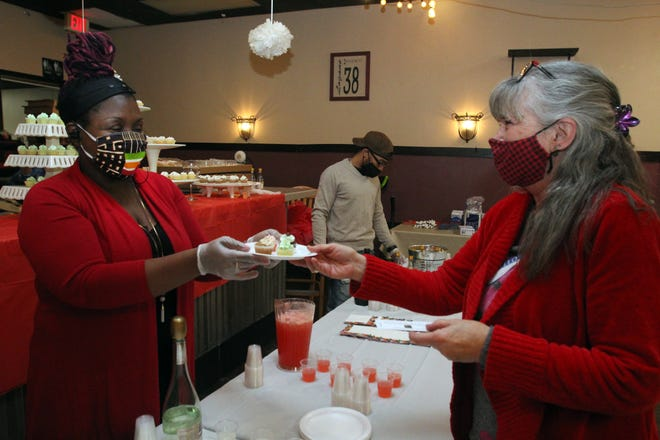 Amber Macklin, left, hands cupcakes to Freya Barger at the Cupcakes and Cocktails fundraiser for CONTACT on Friday, Feb. 19, 2021, at Logan's Bar & Grill in Freeport.