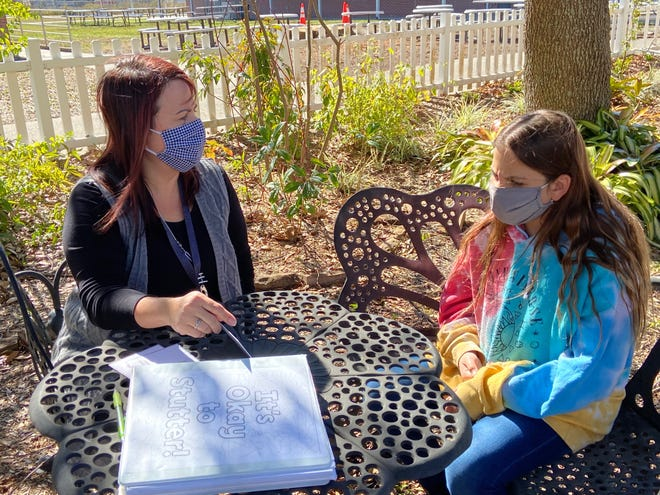 Marie Sepulveda, speech-language pathologist at Snively Elementary School, and Chloe Lucas, 11, talk about strategies to combat stuttering.