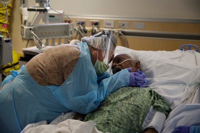 FILE - In this July 31, 2020, file photo, Romelia Navarro, 64, weeps while hugging her husband, Antonio, in his final moments in a COVID-19 unit at St. Jude Medical Center in Fullerton, Calif. The U.S. death toll from COVID-19 has almost topped 500,000 Ñ a number so staggering that a top health researchers says it is hard to imagine an American who hasn't lost a relative or doesn't know someone who died. (AP Photo/Jae C. Hong, File)