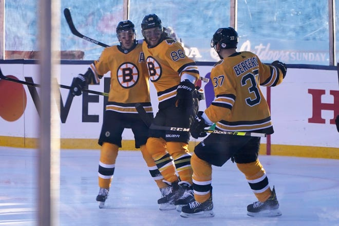 Boston Bruins right wing David Pastrnak (center) celebrates with teammates Brad Marchand (left) and Patrice Bergeron after scoring against the Philadelphia Flyers in the first period of an NHL hockey game in Stateline, Nev., Sunday.
