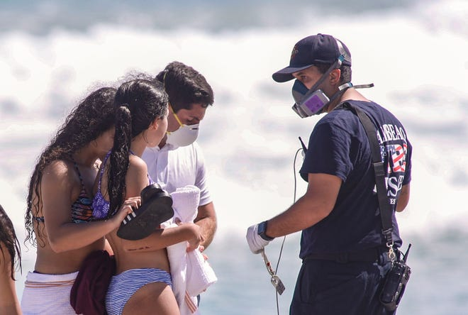 Palm Beach fire rescue workers check on sisters who got caught in a rip current at Midtown Beach on Monday.
