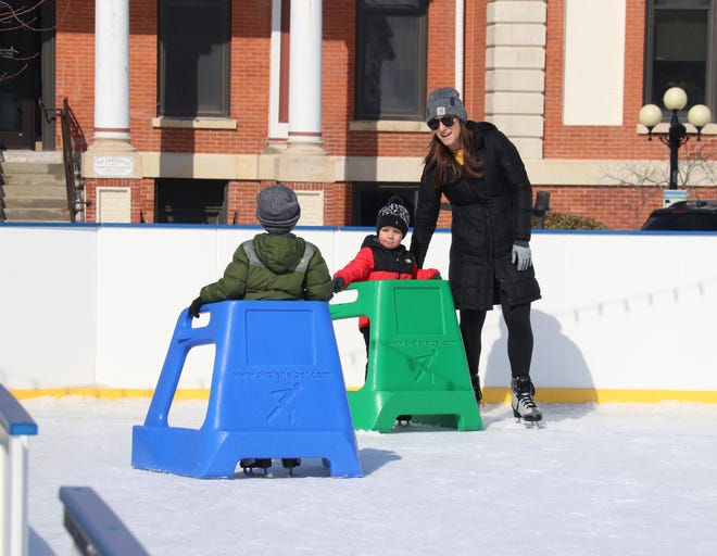 Daniele Schulz of El Paso watches over Gunnar and Bowyn Schulz as the trio enjoyed an afternoon of skating at the downtown outdoor rink in Pontiac.