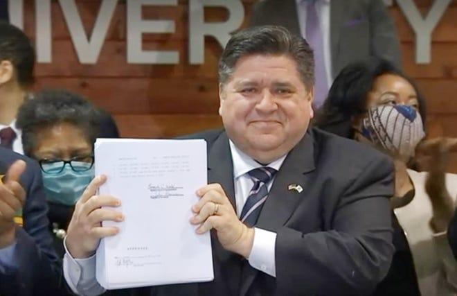Gov. JB Pritzker displays House Bill 3653 after signing it Monday at Chicago State University.