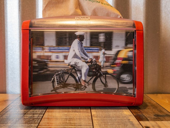 A napkin dispenser at Tiffin Box's West Palm Beach location features India's ubiquitous dabbawalas, the lunch delivery service that takes tiffin-boxed meals to workers.