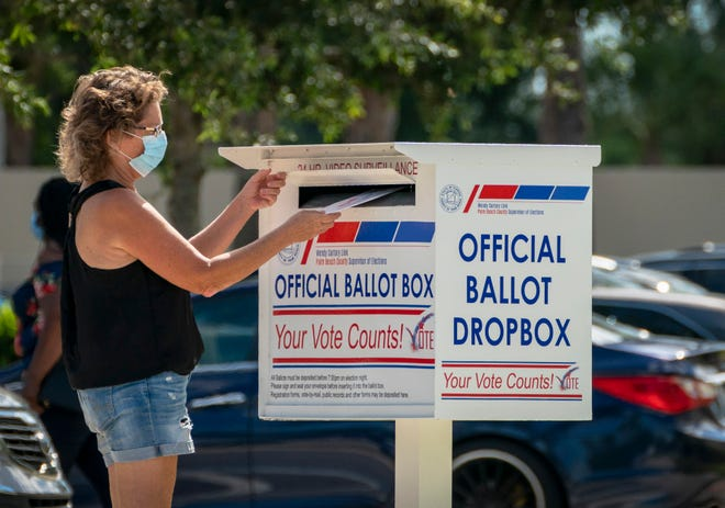 A voter drops off her vote by mail ballot at the Supervisor of Elections office on election day in West Palm Beach in August. GREG LOVETT / PALM BEACH POST