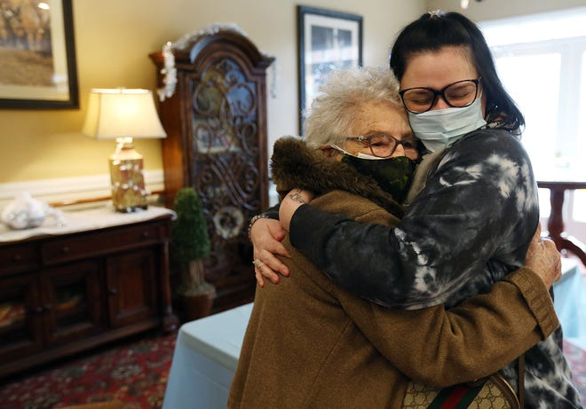 COVID survivor Anna Amalfitano, 87, gets a quick hug from granddaughter Erica Henry on Monday — their first visit in months — at Cherry Hill Manor in Johnston. Amalfitano was the first resident of Cherry Hill to test positive for the virus, which has killed 50 to 54 people there.