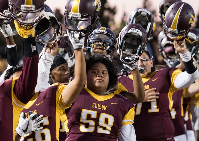 Edison High's Zachary Taamu raises his helmet at the end of the National Anthem before a game against Lodi High on Sept. 22, 2017.