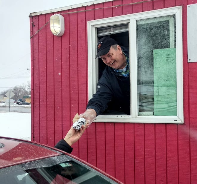 Jim Haavisto waits on a customer at J.D.'s Gourmet Hot Dogs, a drive-up trailer in Canton.