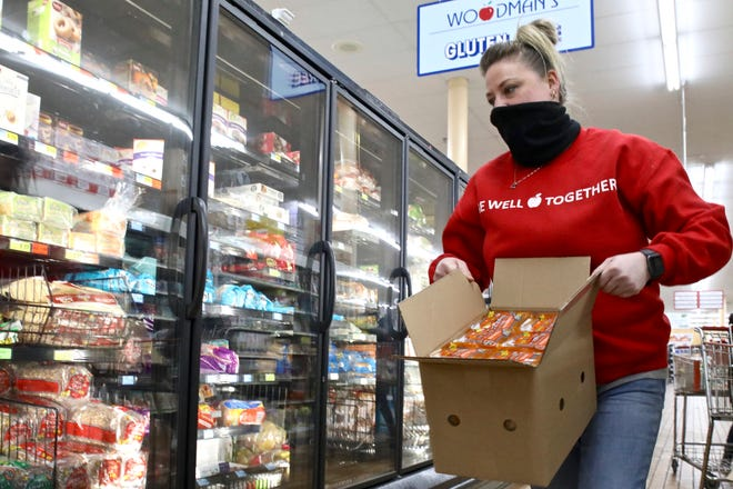 Angela Correll, 35, of Loves Park, refills a freezer Monday, Feb. 22, 2021, at WoodmanÕs Market in Rockford. Correll, a grocery clerk, has worked at the store for almost 17 years.
