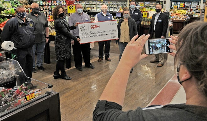 Kim Bateman, Dillons Assistant Communications Manager, takes a photograph of Dillons management as they presented a check to Souper Bowl of Hope campaign to a few of the Project Salina board members for $15,000 at the Sunset Plaza Dillons, 1201 W Crawford Street, on Monday.