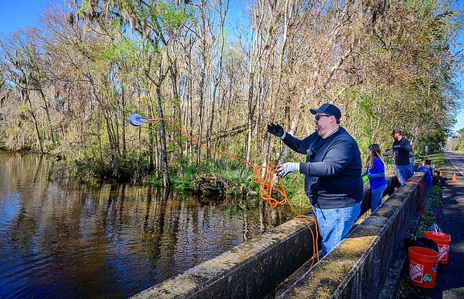 Jason Garcia throws a powerful magnet attached to a rope from a bridge over a creek on County Road 13 in southern St. Johns County on Saturday. Garcia is magnet fishing, a new hobby that uses the magnets to search for metal objects in bodies of water.
