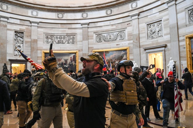 The Department of Justice says that Graydon Young, 54, of Englewood, shown on Jan. 6 in the U.S. Capitol, right of center in a black helmet, was arrested last week.