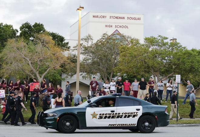 In this Feb. 28, 2018, file photo, a police car drives near Marjory Stoneman Douglas High School in Parkland as students return to class for the first time after a former student opened fire there with an assault weapon.
