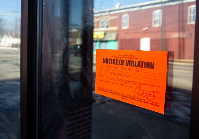 A notice of violation from the City of Springfield Building & Zoning Department was posted on the door of the former beauty supply store at 11th and South Grand Avenue East in Springfield, Ill., Monday, February 22, 2021. A shooting that occurred on Saturday during a party at the former beauty supply store left one person dead and four others injured. [Justin L. Fowler/The State Journal-Register]