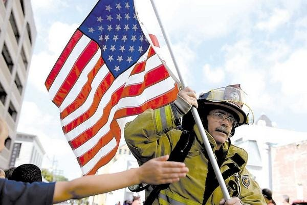 A firefighter carried an American flag as he runs in the 2015 Savannah Mile, a road race benefitting the 200 Club of the Coastal Empire.
