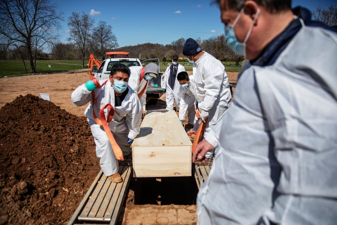 In this April 6, 2020, file photo, gravediggers lower the casket of someone who died of coronavirus at the Hebrew Free Burial Association's cemetery in the Staten Island borough of New York. The U.S. death toll from COVID-19 has topped 500,000 — a number so staggering that a top health researchers says it is hard to imagine an American who hasn't lost a relative or doesn't know someone who died.