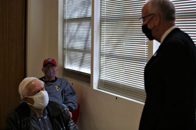 U.S. Sen. Jerry Moran of Kansas, right, tours a COVID-19 vaccine clinic in Topeka and talks with people waiting to get their doses on Feb. 22, 2021.