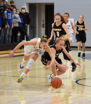 Collins-Maxwell's Alexis Houge and Bree Shaull dive on the court going after a loose ball during the Spartans' 73-27 Class 1A regional quarterfinal victory over the Plainsmen Feb. 16 at Maxwell.