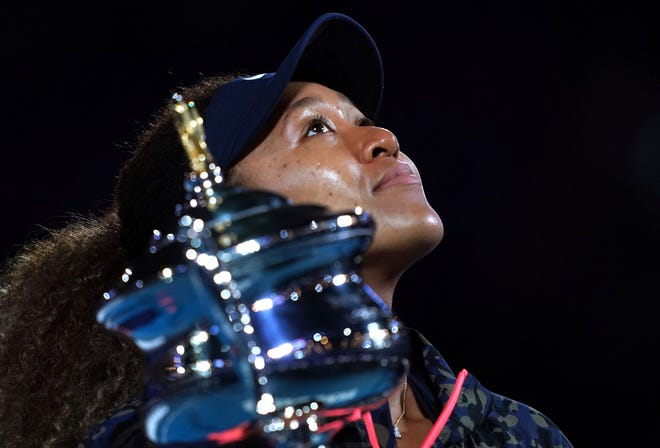 Japan's Naomi Osaka holds the Daphne Akhurst Memorial Cup aloft after defeating Jennifer Brady of the U.S. in the women's singles final at the Australian Open tennis championship in Melbourne, Australia, on Saturday. [AP Photo by Mark Dadswell]