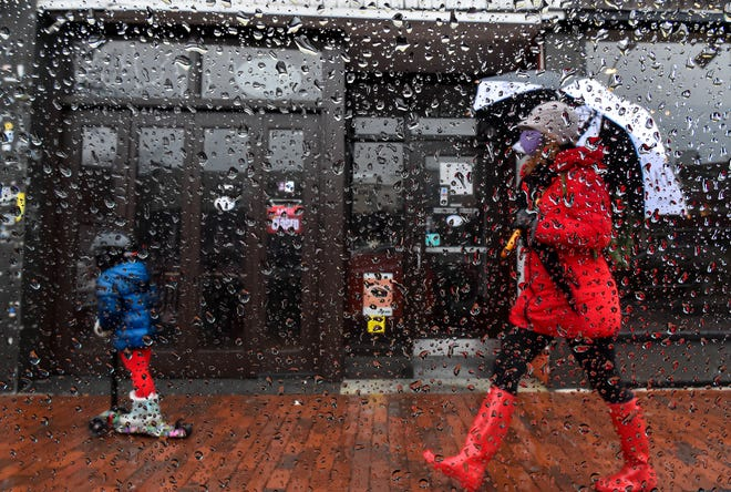 A child rides a scooter and a woman holds an umbrella as they make their way through Davis Square in the rain on Monday, April 27, 2020. [Wicked Local Staff Photo / David Sokol]