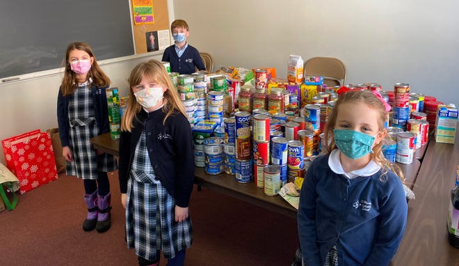 First-graders, from left, Samuel Warren, Julia Savage, Harper Boutin-Stolz and Belle Esposito at St. Mary's Catholic School in Mansfield. The school held a week-long food drive project benefiting the local Hockomock Area YMCA during Catholic Schools Week.
