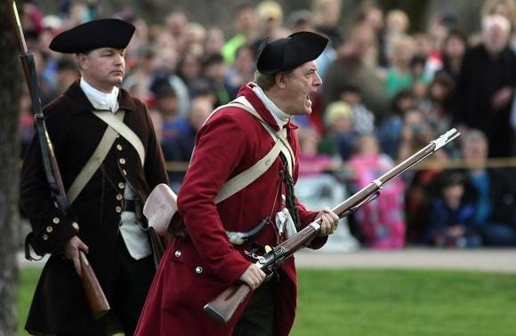"""Barry Cunha, portraying Lt. William Tidd of the Lexington Militia, yells """"you'll not get my gun!"""" to the oncoming British forces on Lexington Green in 2017. Next to him is Steven Conners, portraying Captain John Parker."""