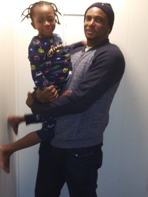 Donnell Johnson holds his son, also named Donnell. The family was homeless and struggling to obtain Donnell's medication, and Catholic Charities helped them get the medicine their son needs, and helped them secure personal documents and housing.