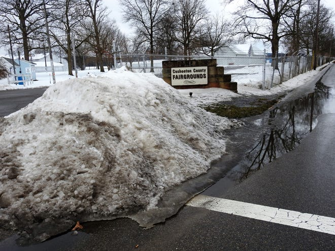 A melting pile of snow at the entrance of the Coshocton County Fairgrounds with water runoff into the street. Rapid melting of snow as temperatures warm can cause issues like flooding, icing and potholes.