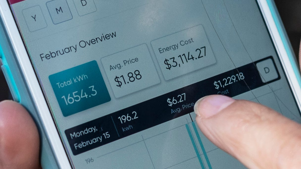 Ivet Cantu, 45, points to her electricity bill from Griddy energy on an app showing her energy cost of $3,114.27, during recent severe cold weather outside of her home in Dallas, on Friday, Feb. 19, 2021.(Ben Torres/The Dallas Morning News via AP)